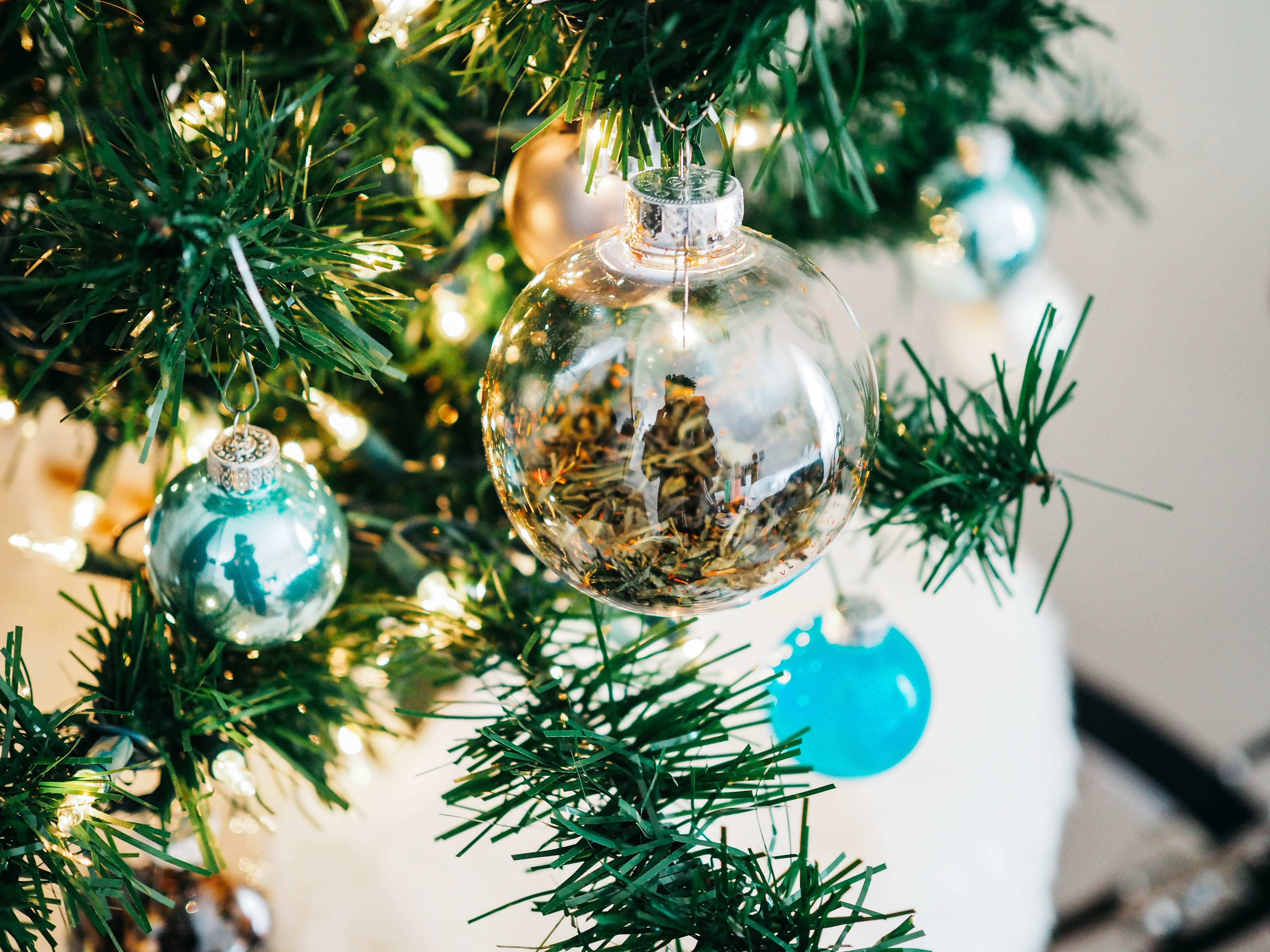 clear and teal glass baubles hanged on lighted Christmas tree