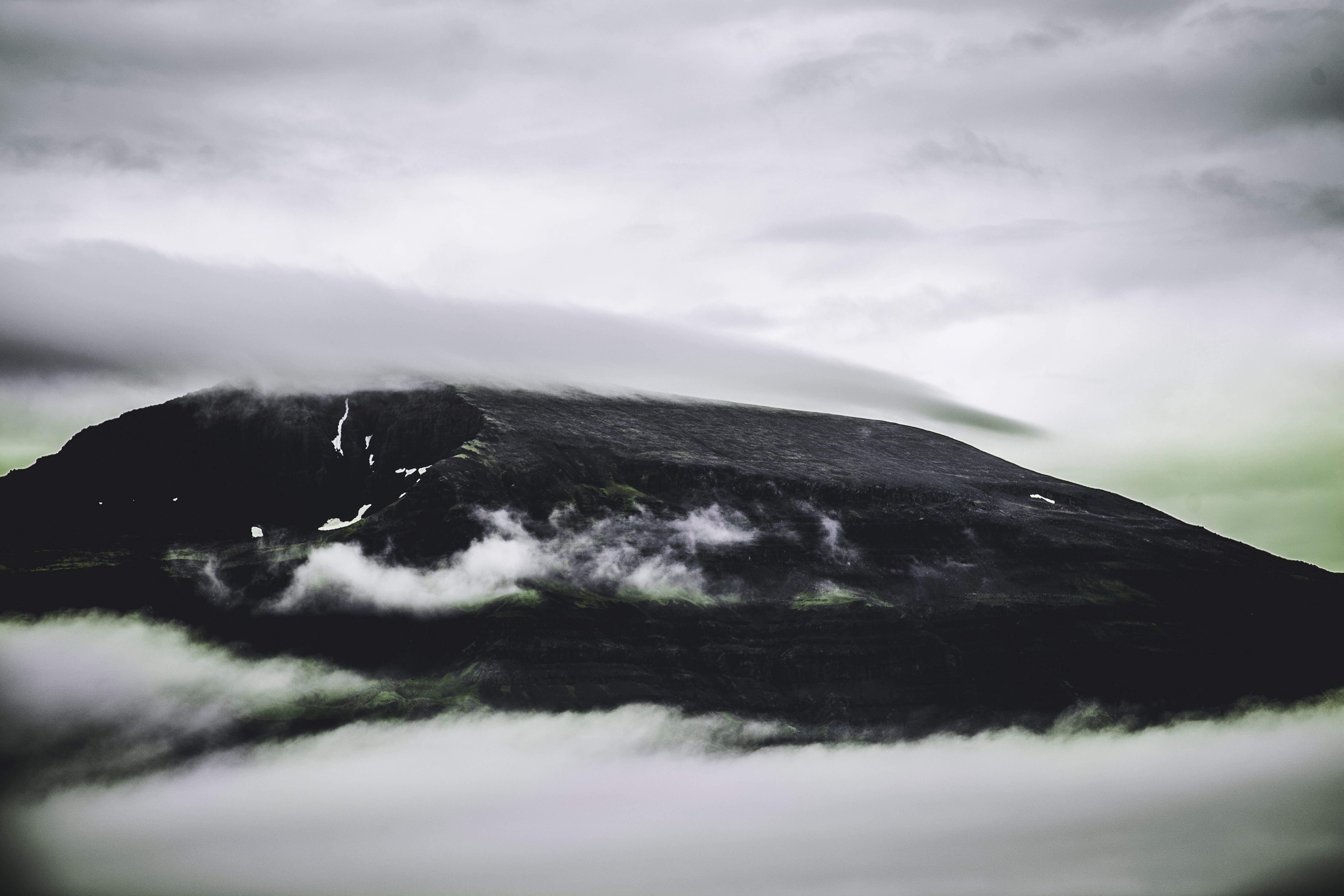 black mountain covered with clouds during daytime