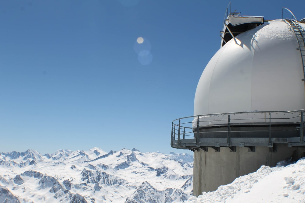 round white building structure in snow capped mountain