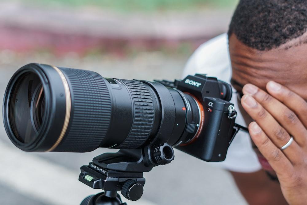man looking on DSLR camera