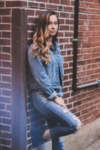 woman leaning on brick wall