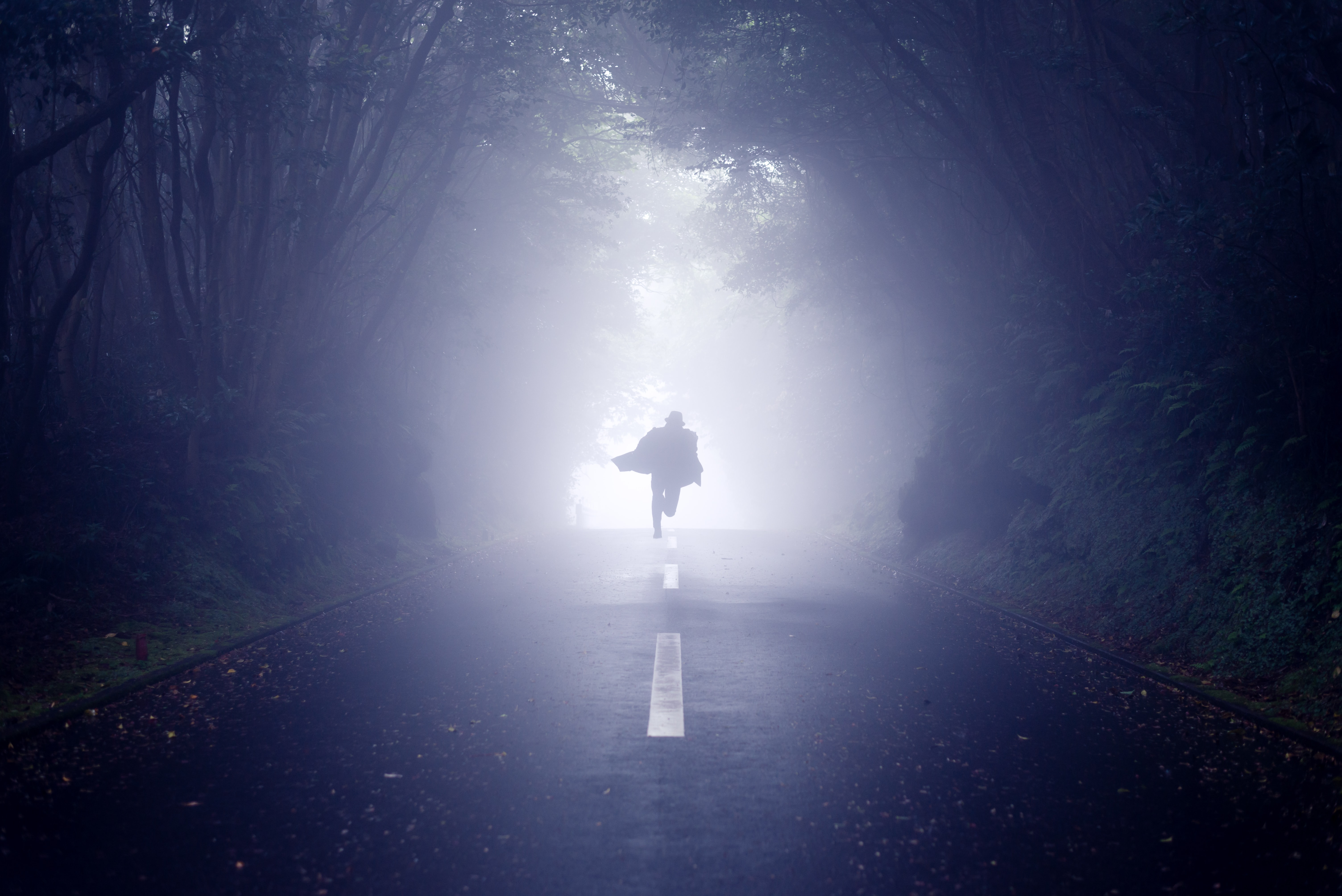 person running road between trees