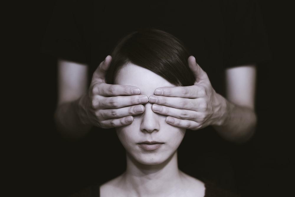 person covering the eyes of woman on dark room