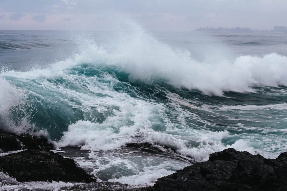 ocean waves hitting rock in beach