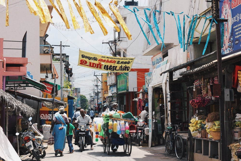 people walking in narrow street with full of food stalls during daytime