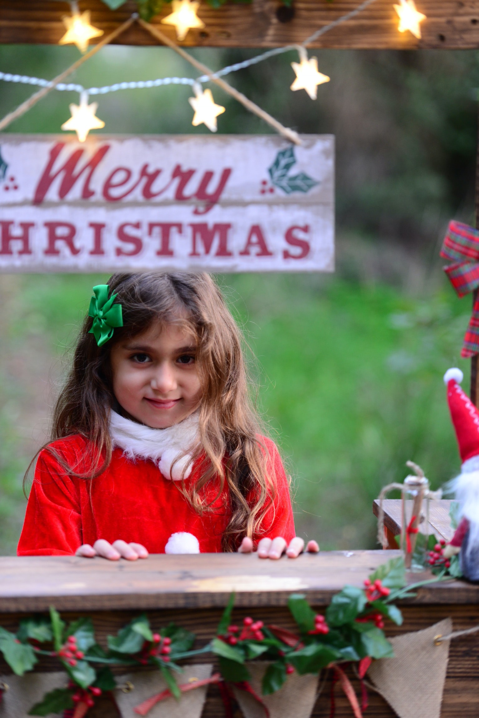 girl standing near merry christmas signage during daytime