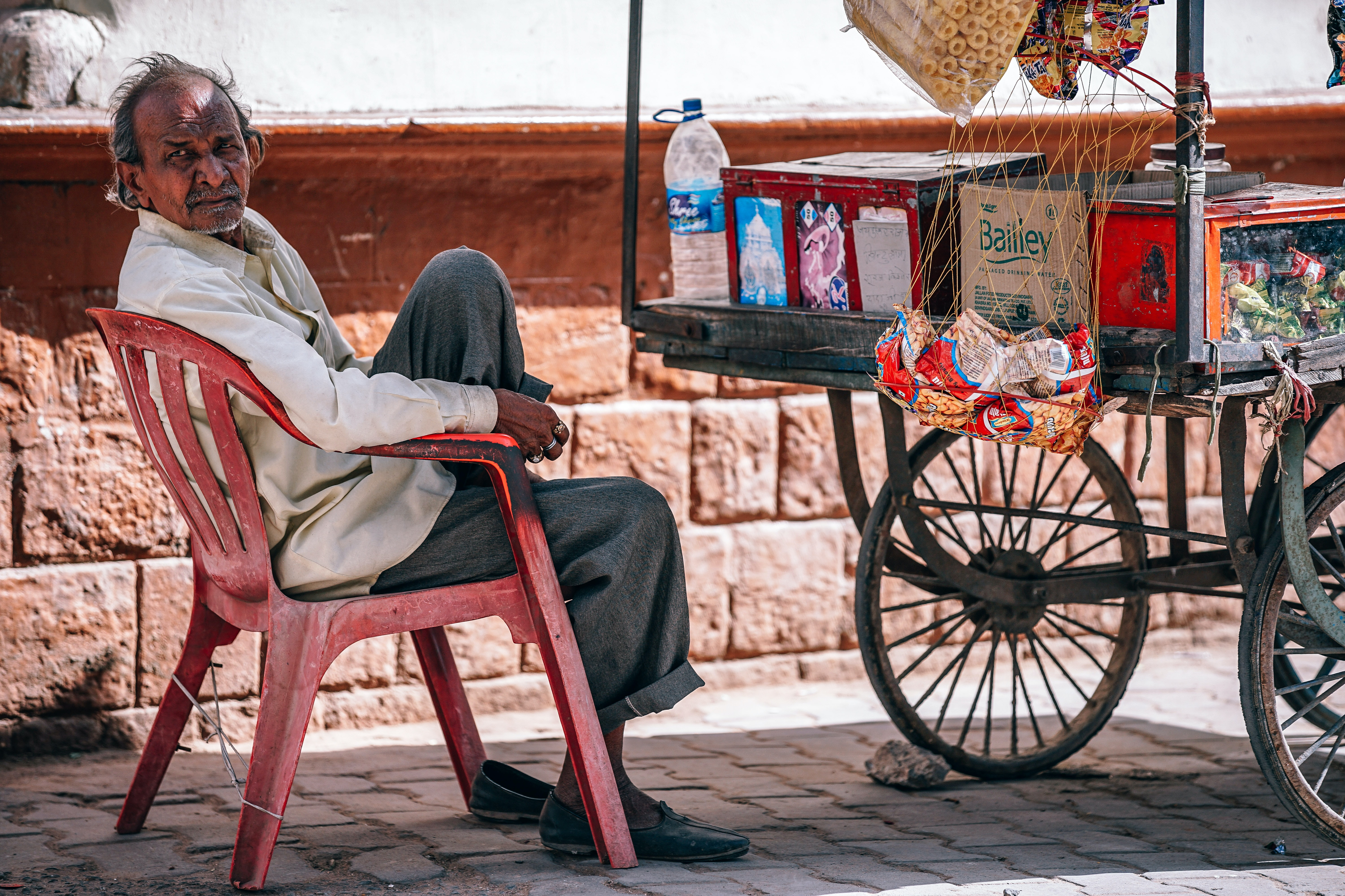 man sitting on chair beside food cart