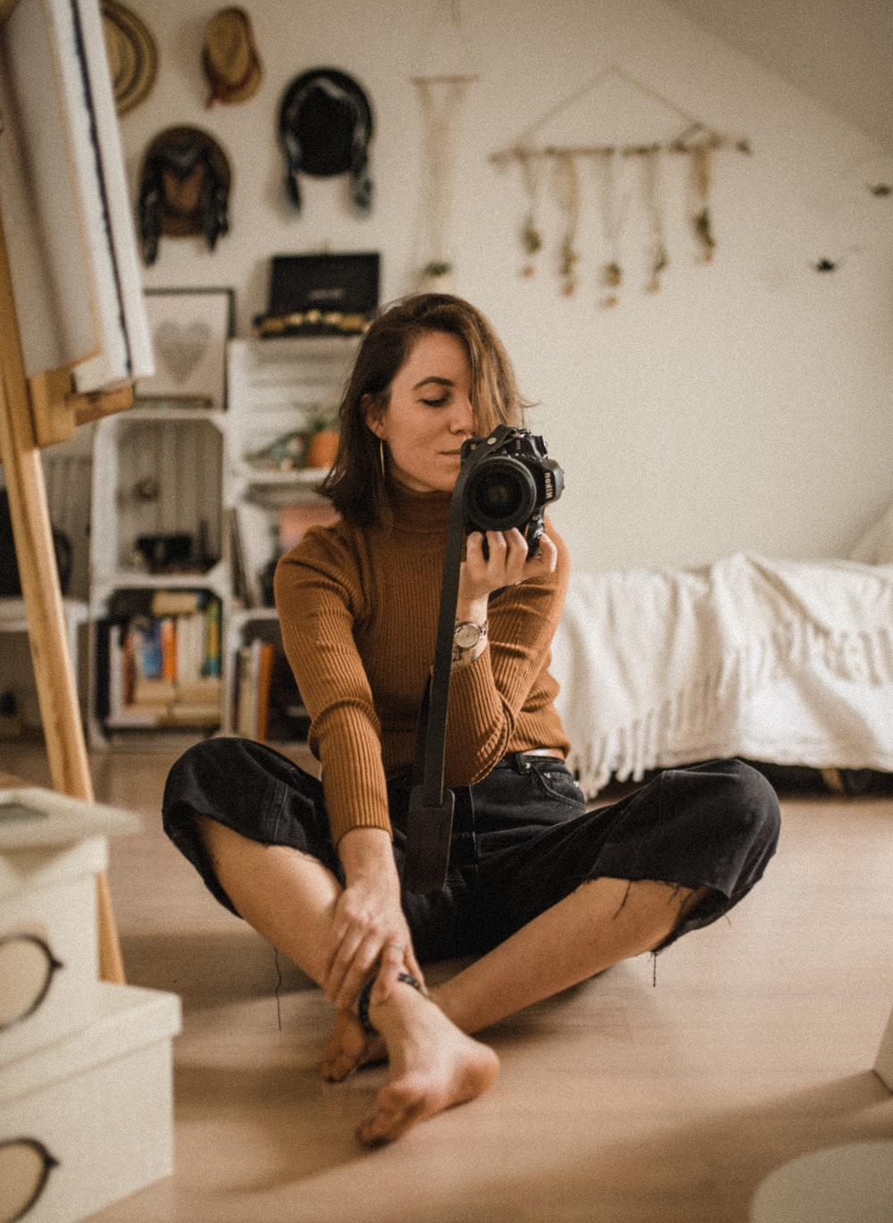 woman sitting on brown wooden floor while holding black DSLR camera in room