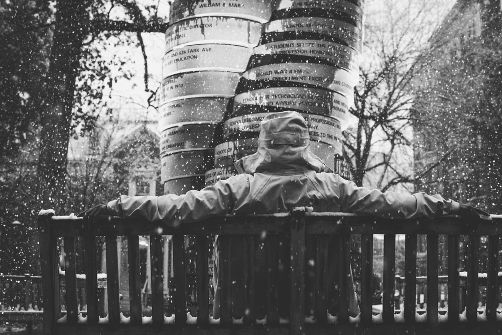 grayscale photography of person sitting on bench