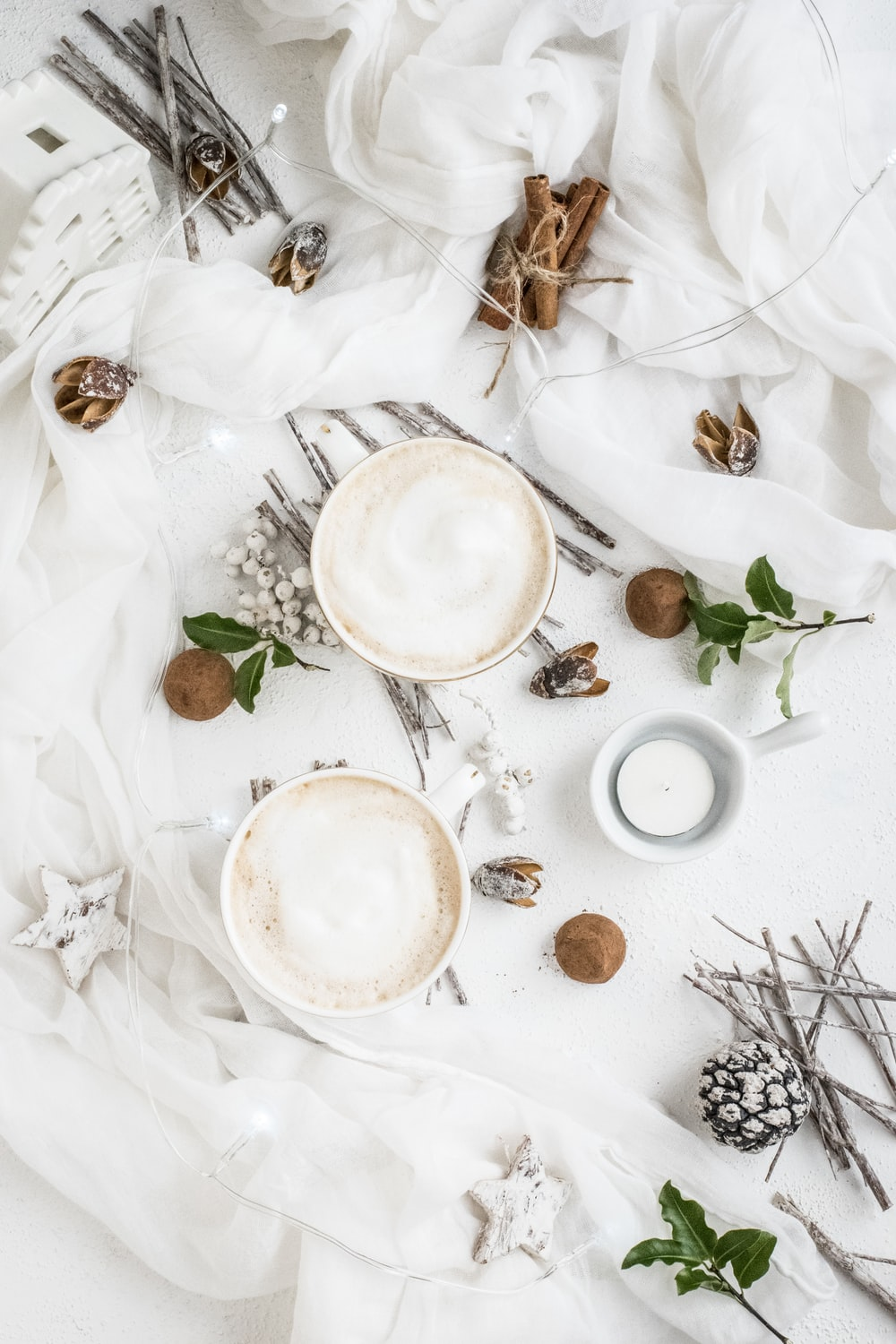 two white ceramic cups on white textle