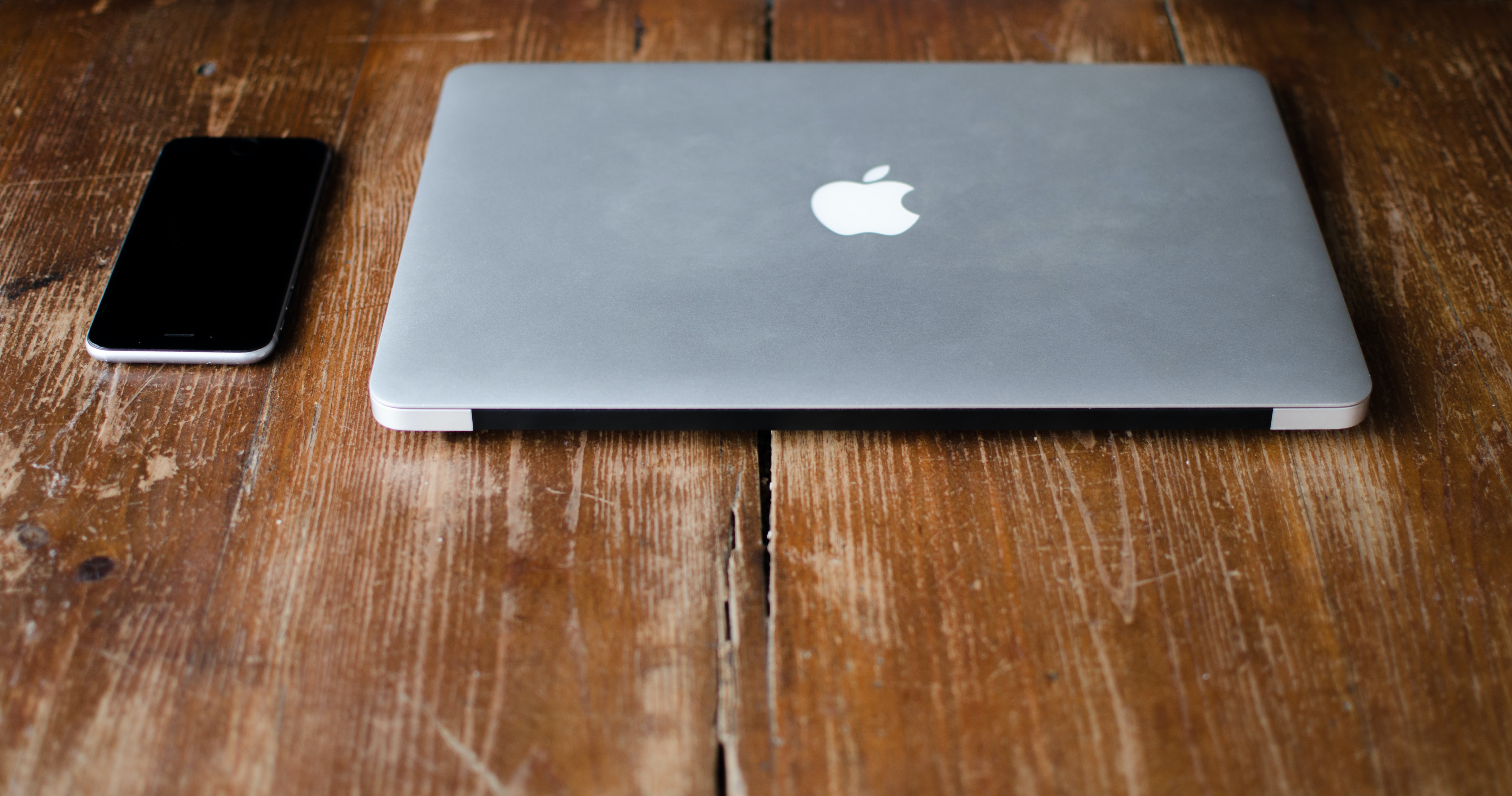 photo of MacBook Pro beside black Android smartphone