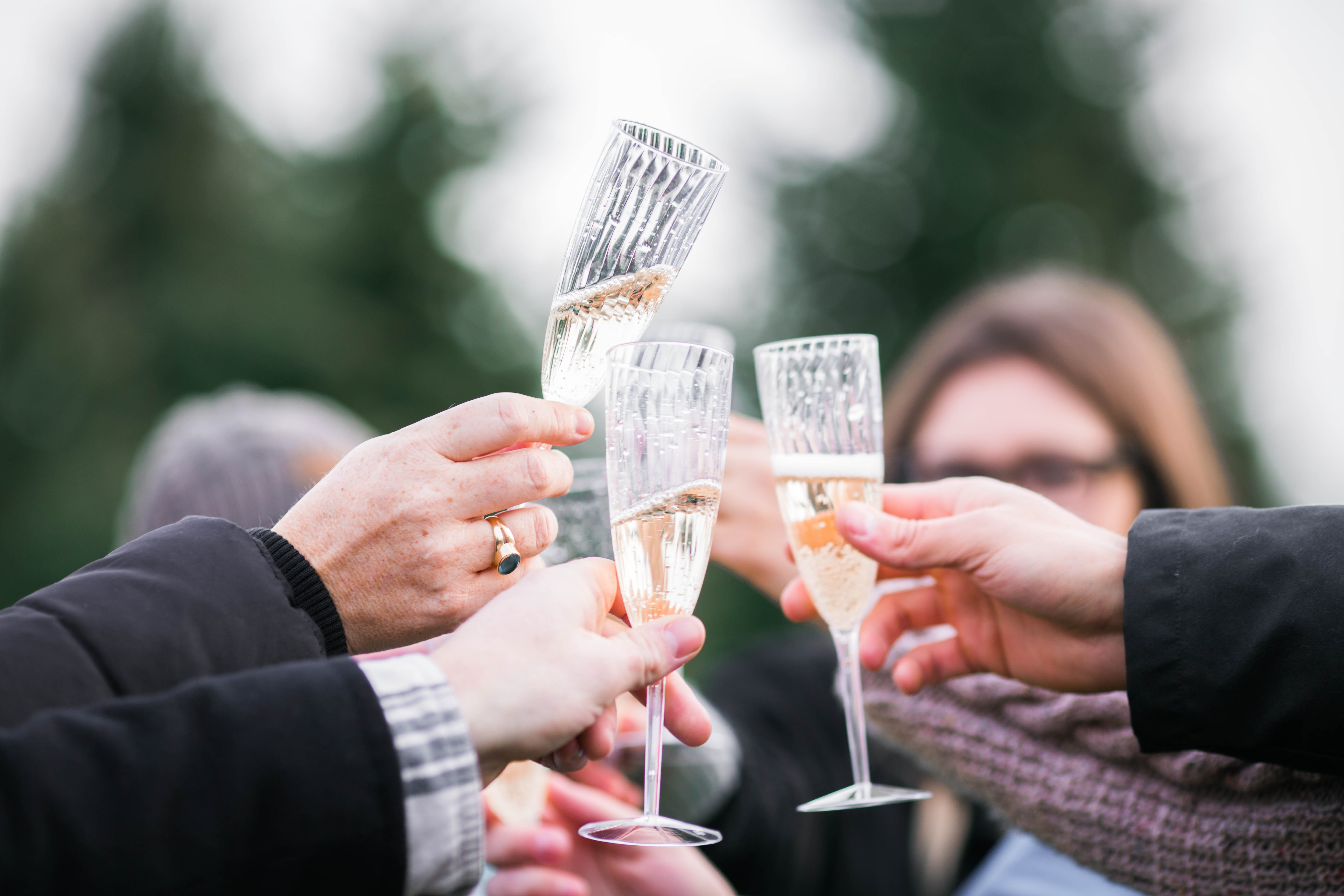 people holding clear champagne glasses