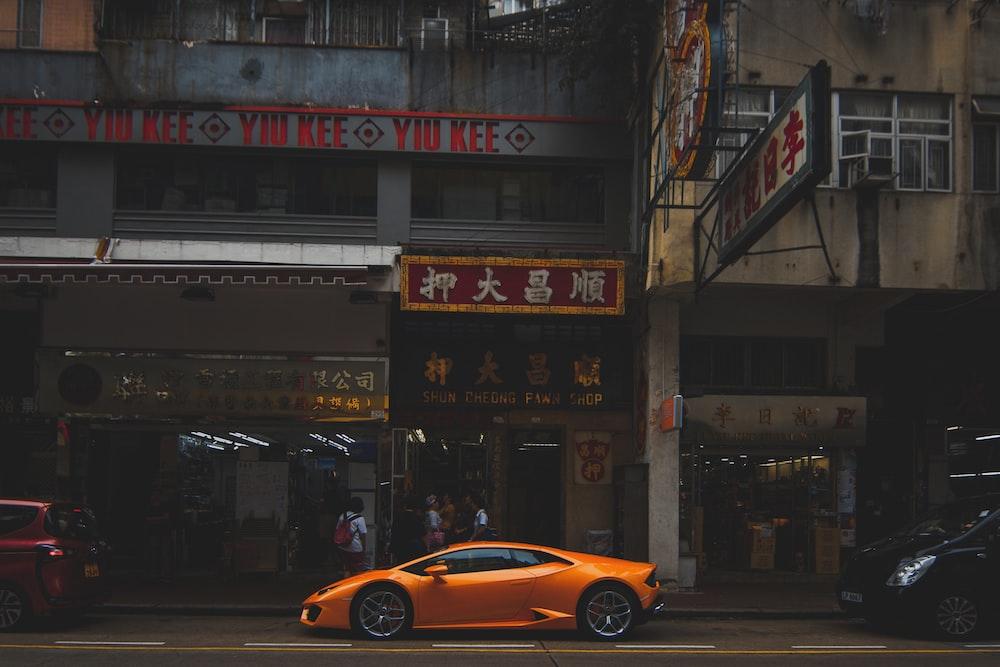 orange Lamborghini Aventador parked infront of restaurant