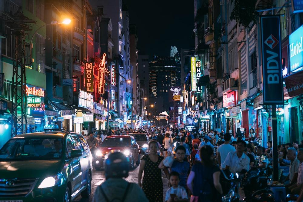 group of people walking on street during nighttime