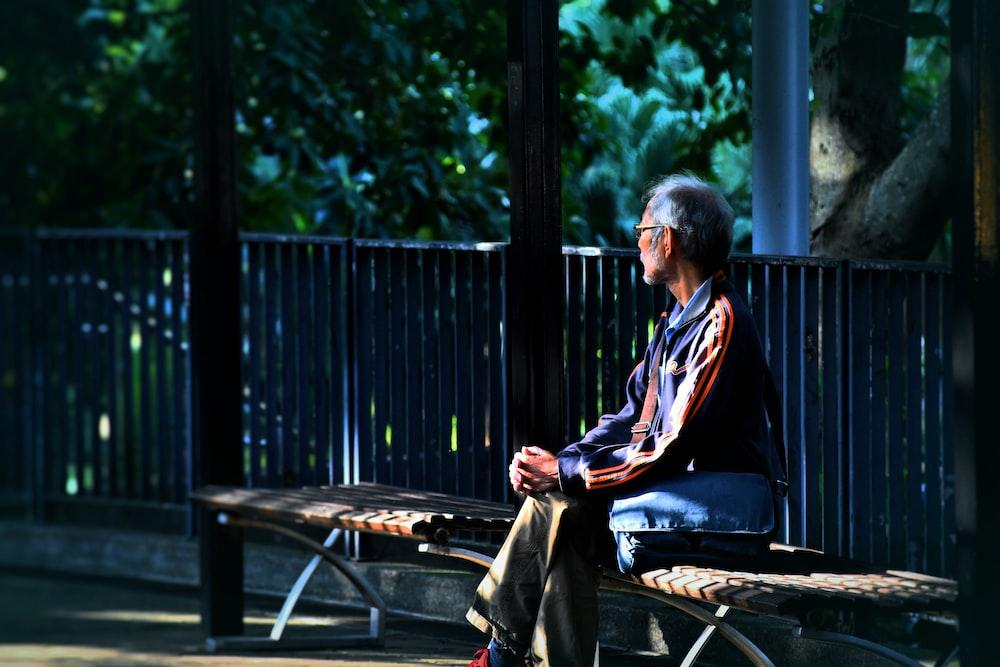 man sitting on wooden bench