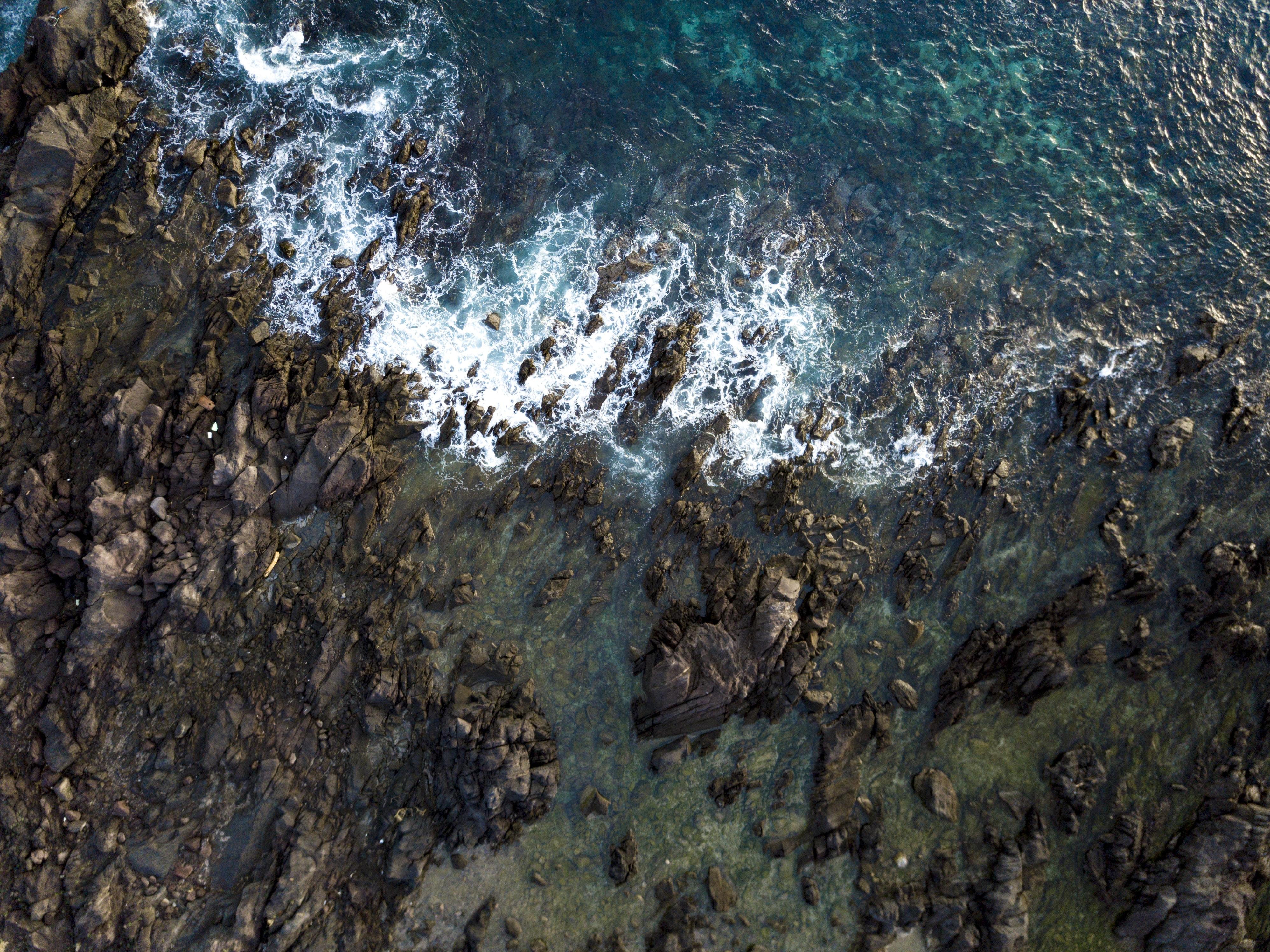 bird's eye view photo of rocks near body of water