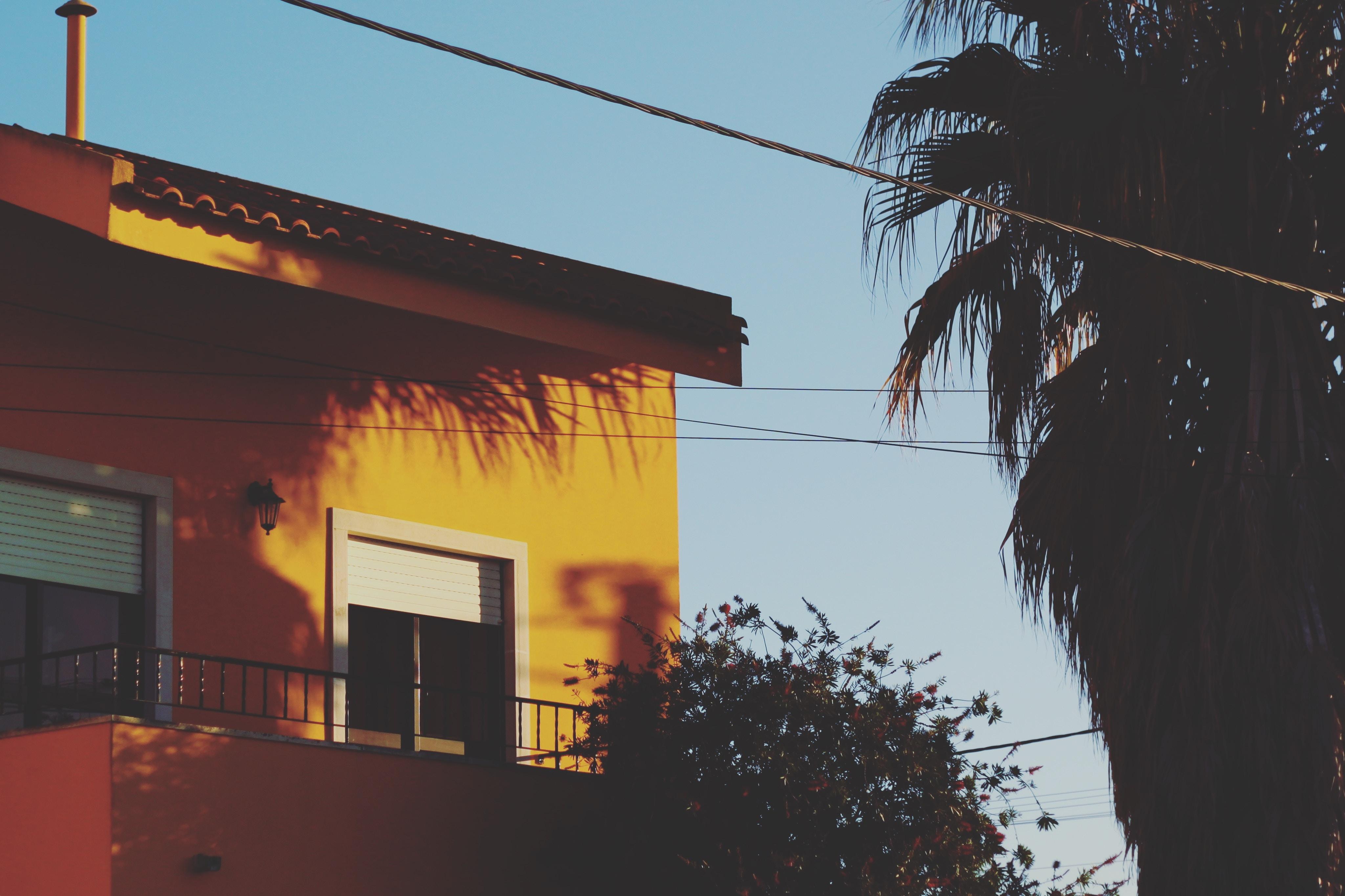 yellow concrete house beside tree