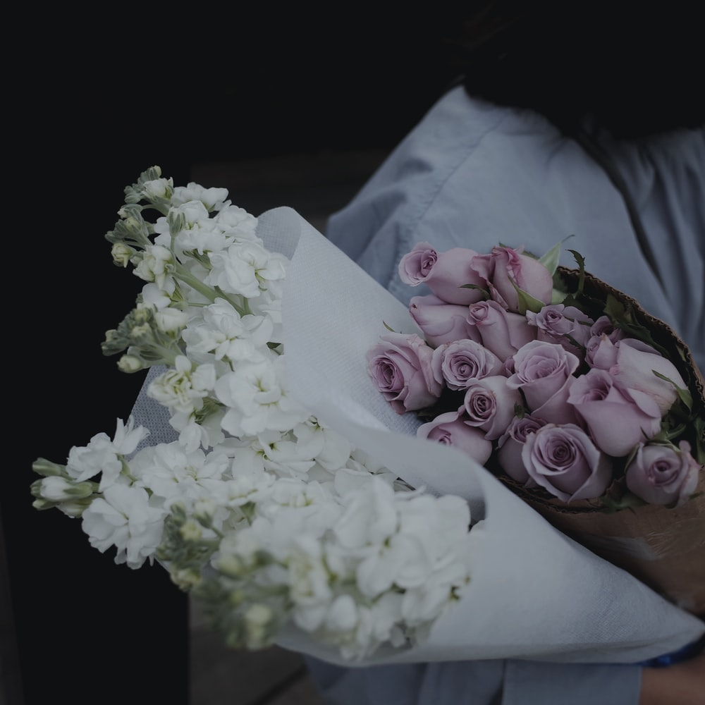 person holding purple and white flower bouquet
