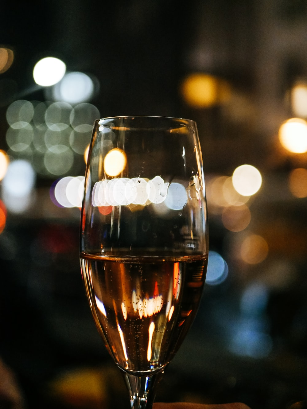 bokeh photography of clear long-stem wine glass
