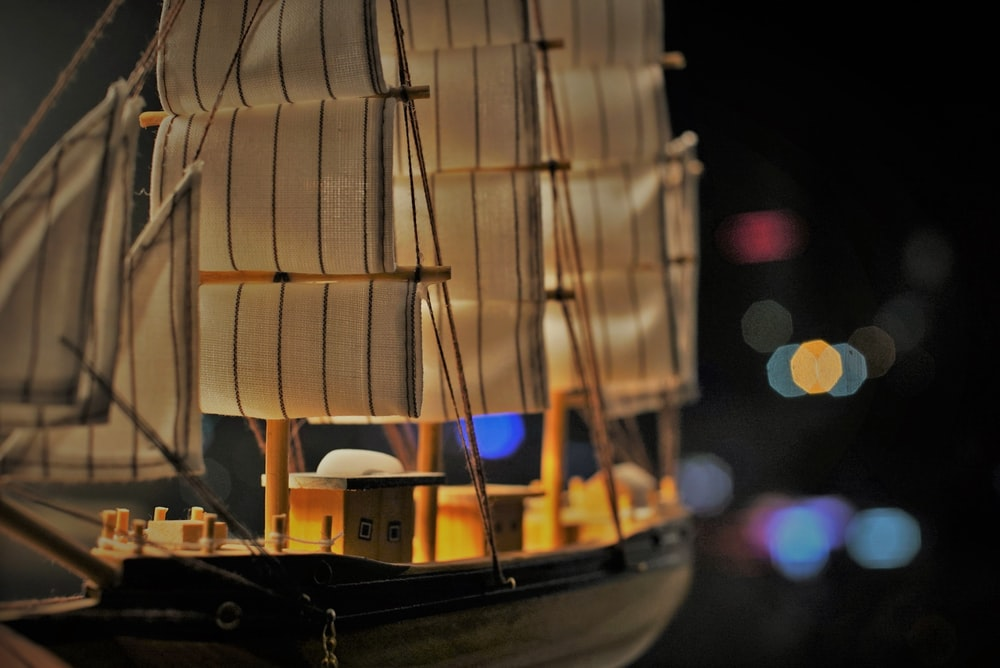shadow depth of field photography of sailboat miniature