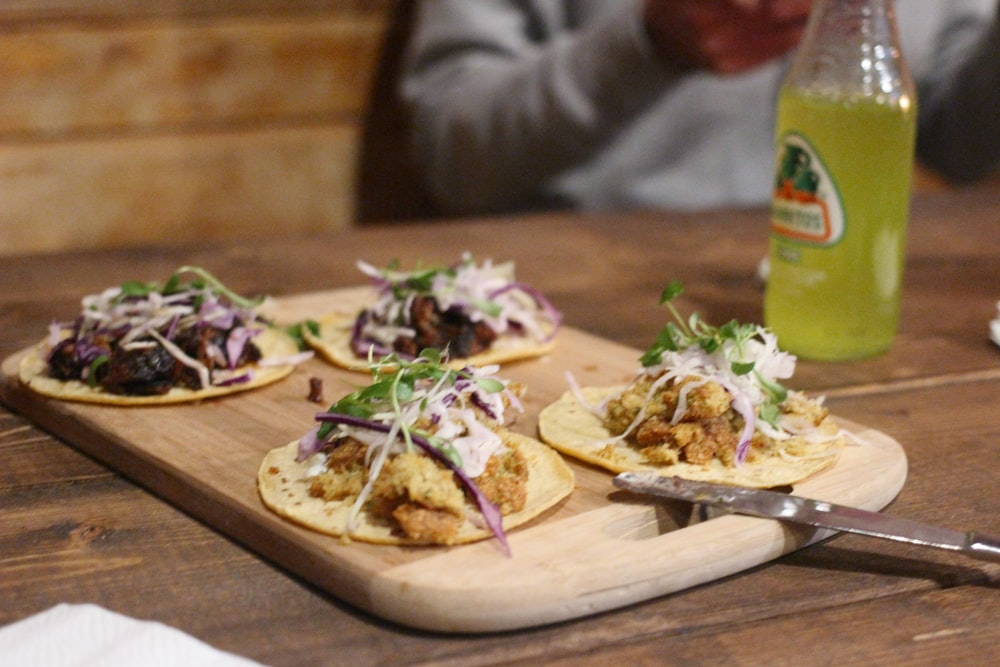 board of four soft tacos on table