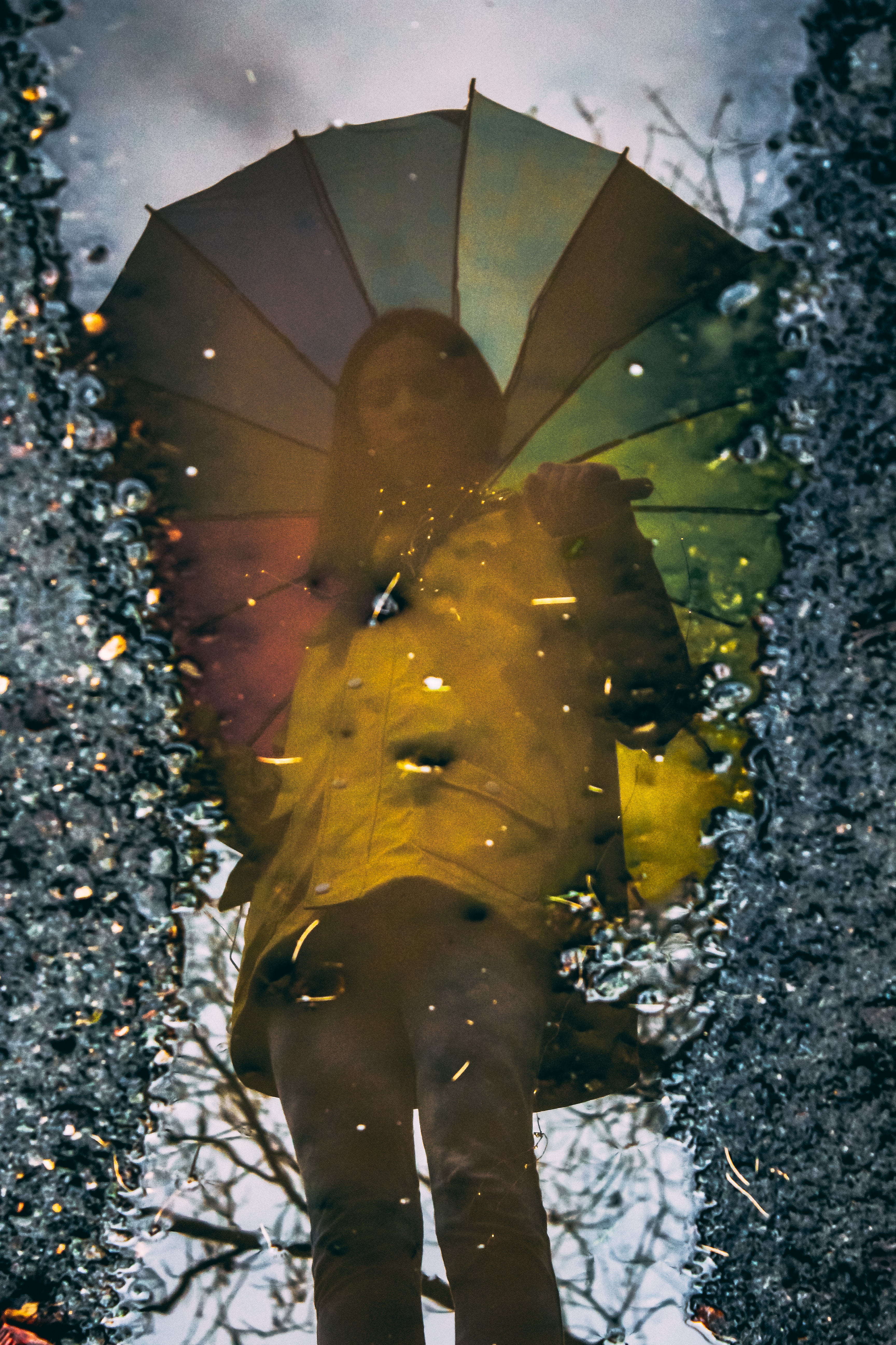 reflection photography of woman standing while holding umbrella