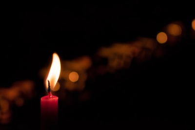 selective focus photography of red candle candle teams background