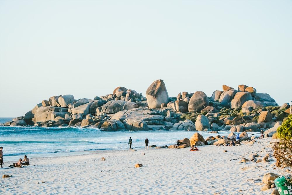people walking on sand near beach