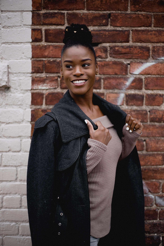 woman in brown tube top under black jacket