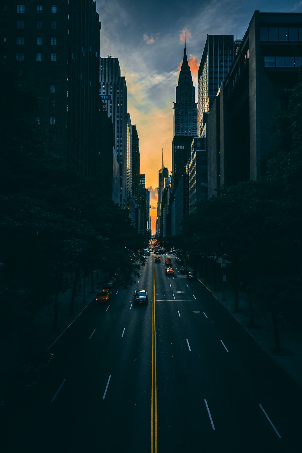 low light photography of vehicle crossing road between high-rise buildings