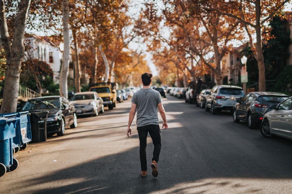 man walking on road between parked vehicles