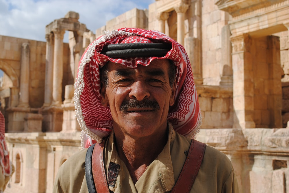 close-up photo of man wearing keffiyeh behind concrete building