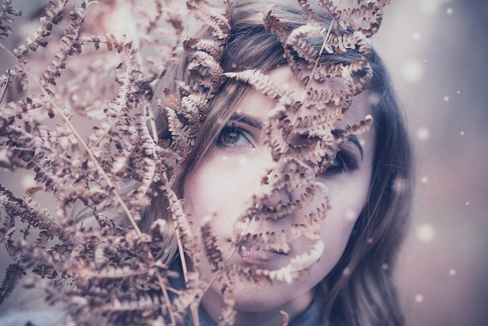 woman behind brown plant