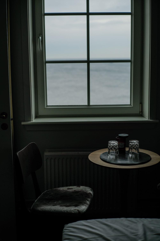 round brown wooden table near window