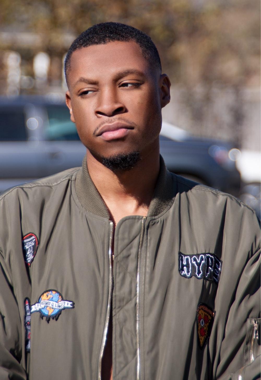 man wearing gray bomber jacket