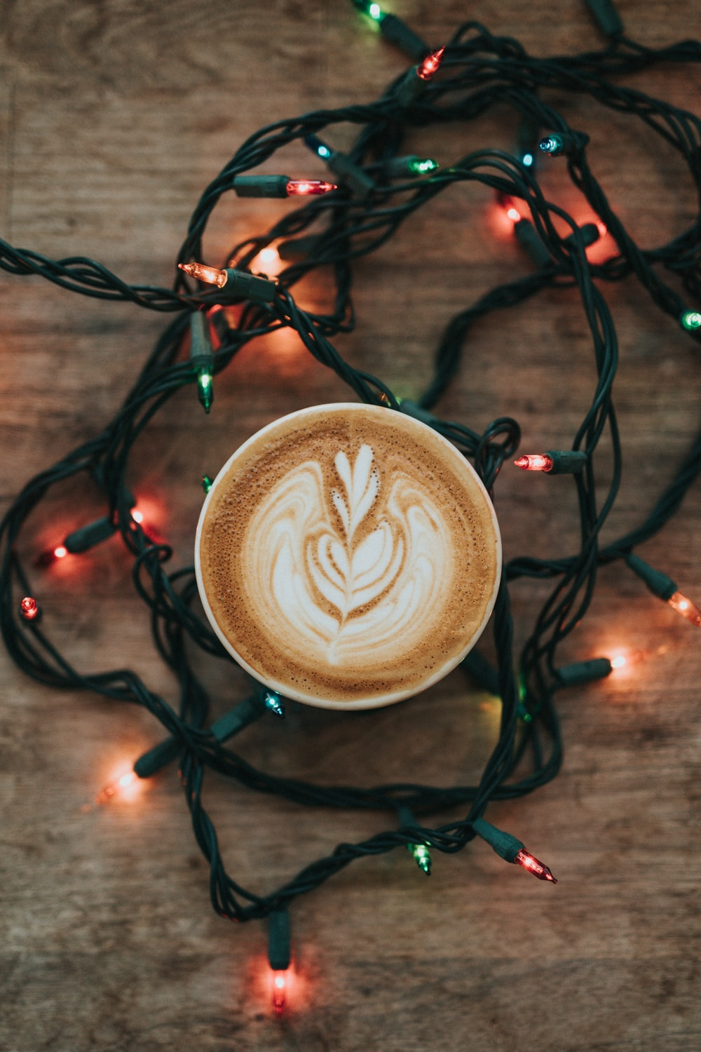 cup of cappuccino and turned on string lights on brown wooden surface