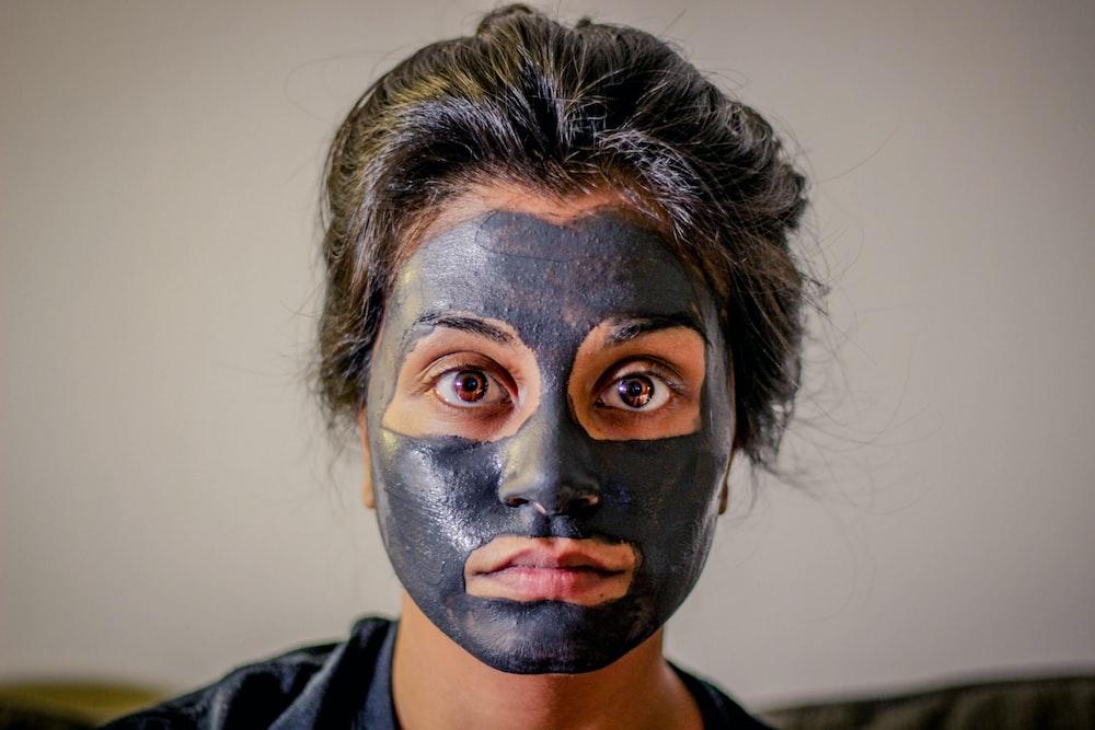 灰色の顔のマスクを持つ女性