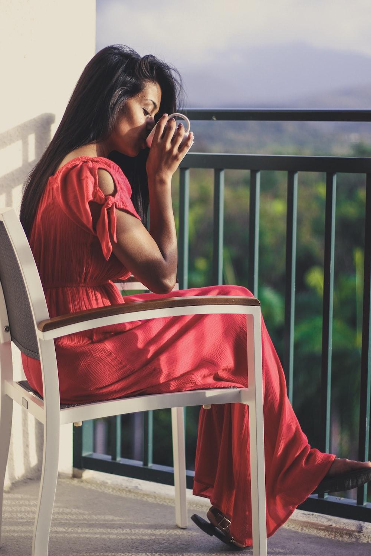 woman holding mug sitting on white armchair