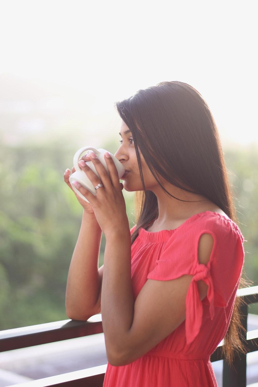 woman drinking on white ceramic mug