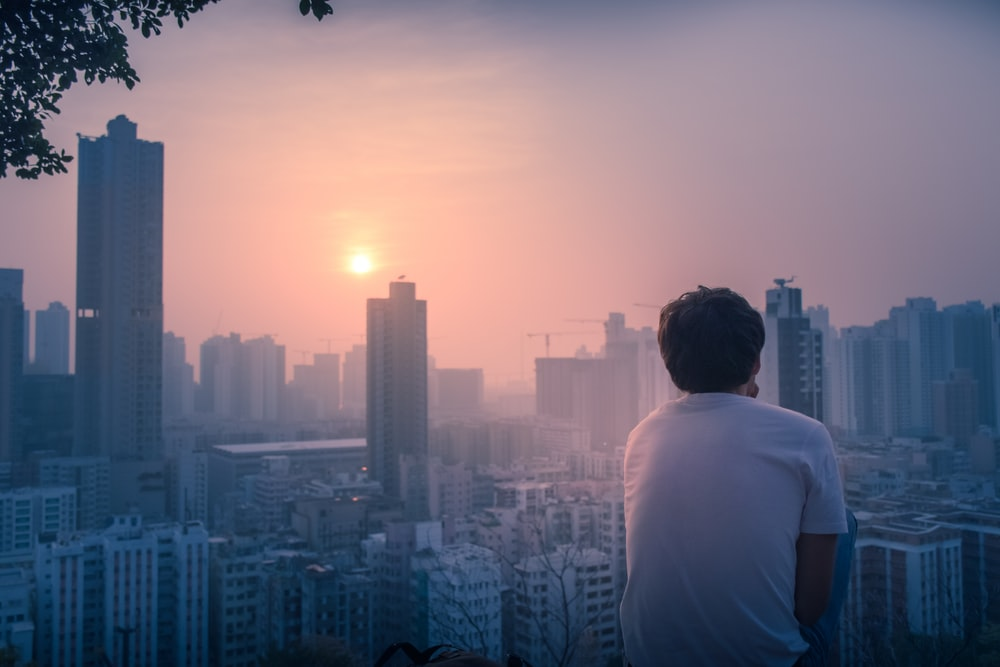 back view of man looks the cityscape at daytime