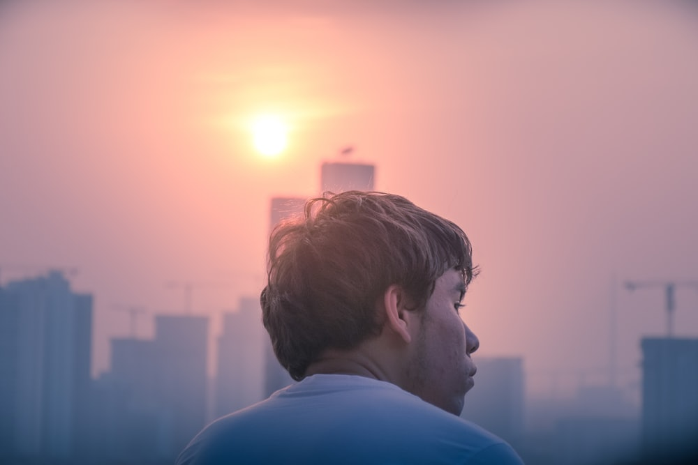 man wearing white shirt overlooking city buildings golden hour photography