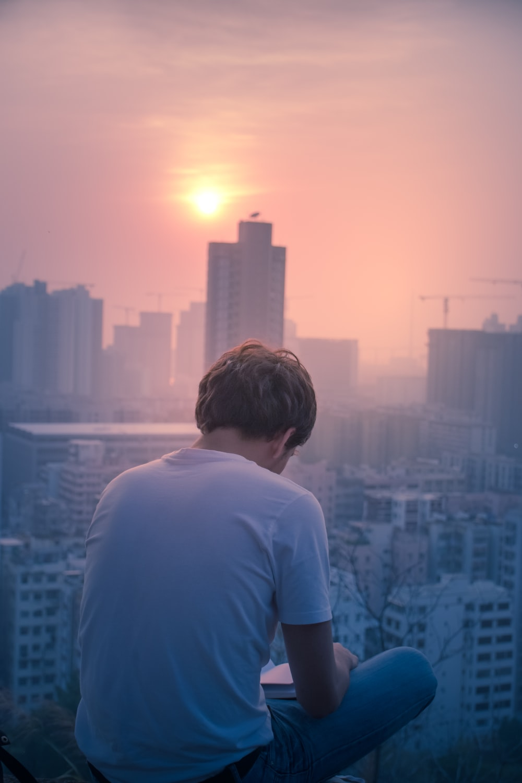 sitting man wearing white shirt reading book overlooking city
