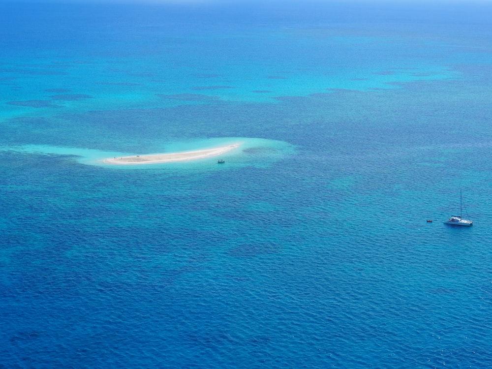 high-angle photography of boat near island