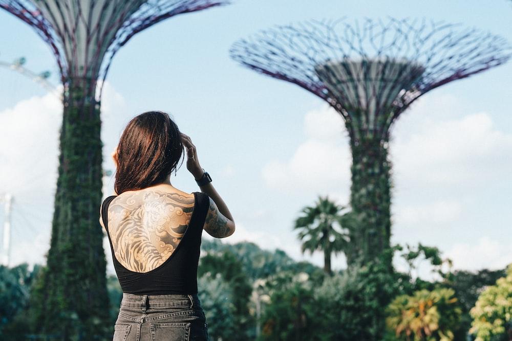 woman in black top standing near garden painting