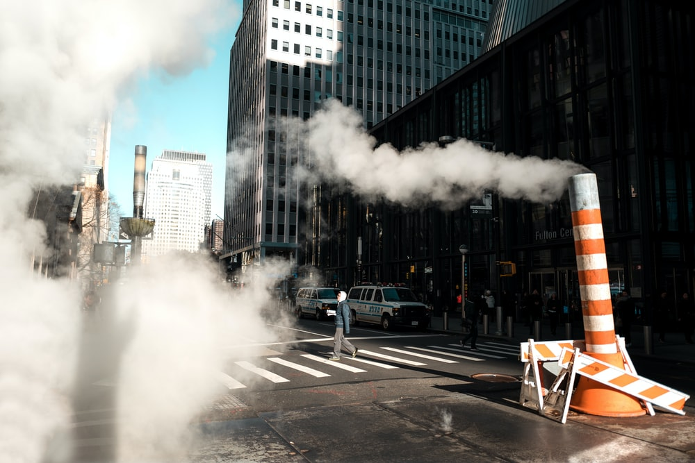 white and orange pedestal road sign with smoke beside building