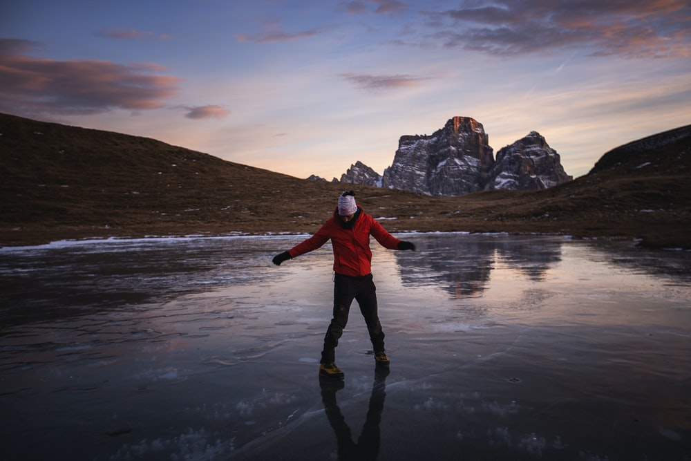 person standing on frozen body of water