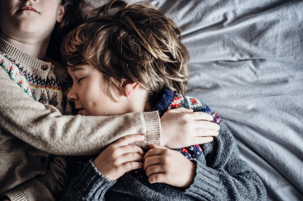 girl and boy lying on bed wearing brown and grey sweatshirts
