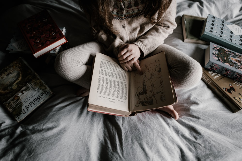 person sitting on bed reading book