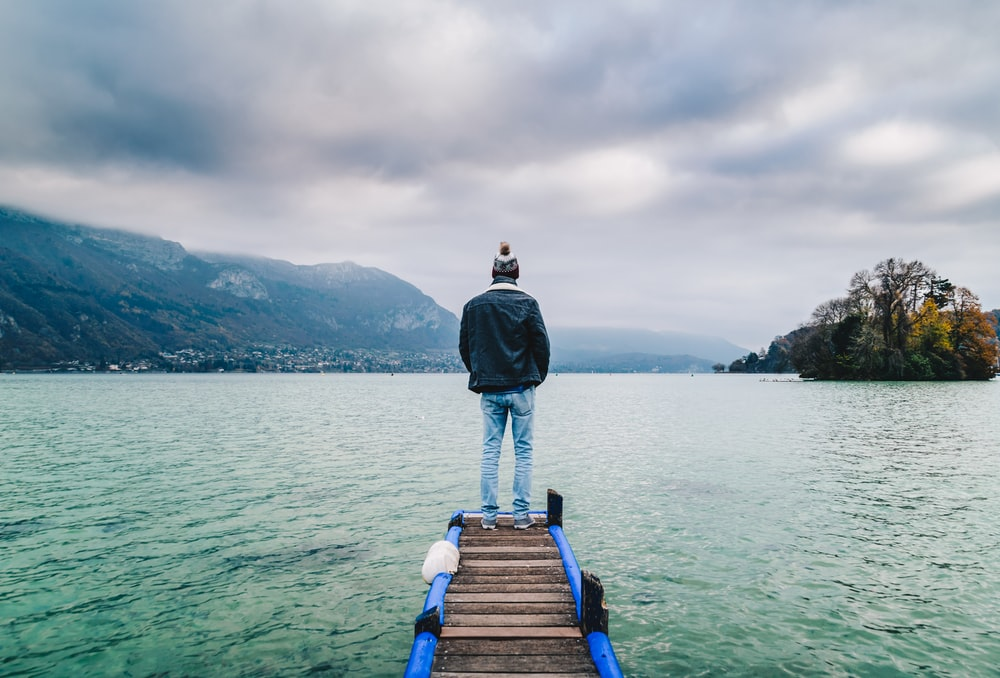 man standing on edge of dock facing mountains
