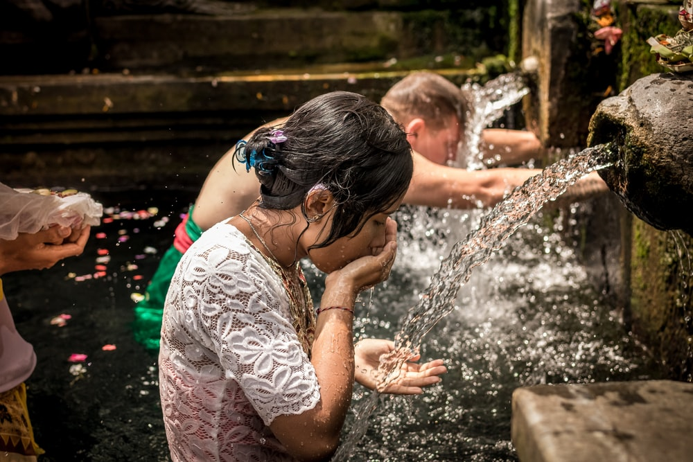 an and woman washing in water fountain with free-flowing water
